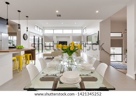 CANBERRA, AUSTRALIA – JUNE 6, 2018: Spacious kitchen furnished with chairs, table, stools, sink, island and large fridge extending into the lounge room in a modern home #1421345252