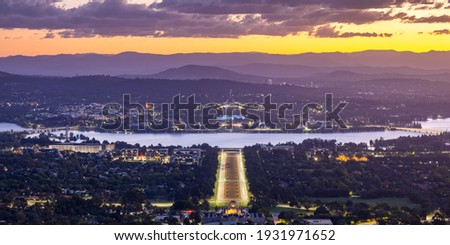 Canberra Australia viewed from Mount Ainslie at sunset looking down on the Australian War Memorial and ANZAC Parade towards Lake Burley Griffin with Parliament House behind and the suburbs of Canberra