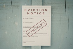 Canceled Foreclosed or eviction notice on a main door with blurred details of a house with vintage filter