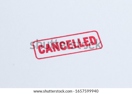 Cancelled stamp close up and isolated on white background. Cancelation message in red ink with border. Textured lettering on craft paper. Photo stock ©