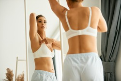 Cancer aware young woman looking herself in a mirror while doing breast self-examination at home.