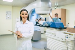 Cancer treatment in a modern medical private clinic or hospital with a linear accelerator. Professional doctors team working while the woman is undergoing radiation therapy for cancer