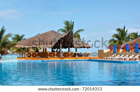 Cancun swimming pool and palapa overlooks ocean.