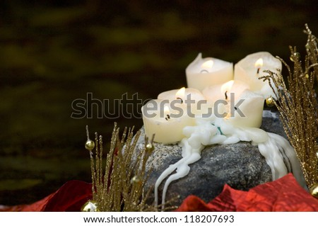Candels sitting on rock with christmas decorations near stream