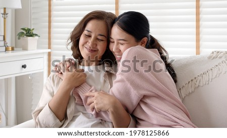 Candid attractive beautiful mum sit at cozy sofa couch living room in family moment grown child kid celebrate joy good warm time kiss relationship with retired overjoy lady girl health life insurance.