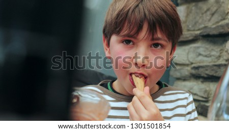 Candid authentic real life of child eating ice-cream. Kid eats chocolate dessert #1301501854