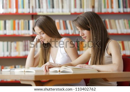 Candid capture of a pair of university students in the college library - stock photo