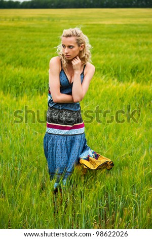 Candid carefree adorable woman in field with at summer sunset wearing bright colorful dress
