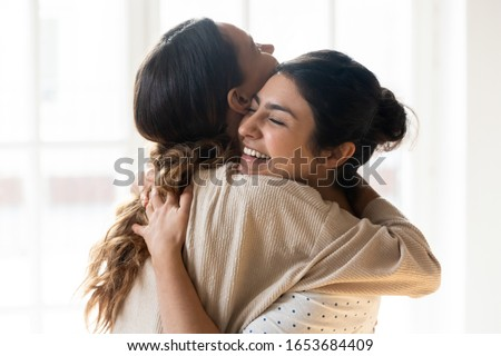 Candid diverse girls best friends embracing standing indoors, close up satisfied women face enjoy tender moment missed glad to see each other after long separation, friendship warm relations concept