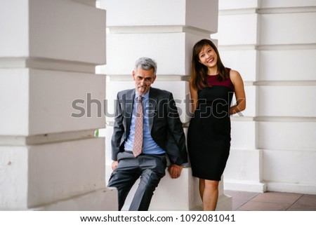Candid, funny and light-hearted business portrait of an Asian Chinese woman and a mature Caucasian man leaning against a pillar of a legal-looking building. #1092081041