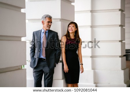 Candid, funny and light-hearted business portrait of an Asian Chinese woman and a mature Caucasian man leaning against a pillar of a legal-looking building. #1092081044
