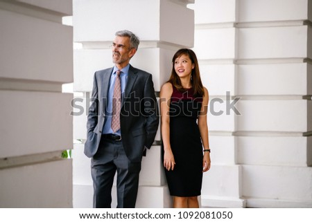 Candid, funny and light-hearted business portrait of an Asian Chinese woman and a mature Caucasian man leaning against a pillar of a legal-looking building. #1092081050