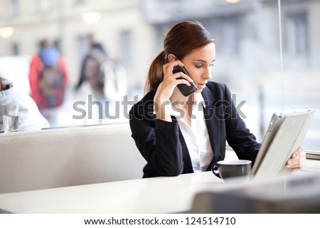 Candid image of a businesswoman working in a cafe. Selective focus.