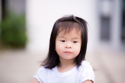 Candid in the face of a weary and lonely child from social distancing isolation. From not having friends of the same age playing. One little Asian girl aged 3 - 4 years old.