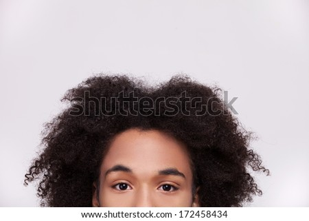 Candid look. Cropped image of cheerful African teenager looking at camera while isolated on grey background #172458434