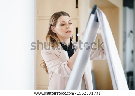 Candid moment, female manager presents new project plan to colleagues at meeting, explaining ideas on flipchart to coworkers in office.