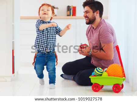 candid moment of happy father playing with cute baby son at home, family games #1019027578