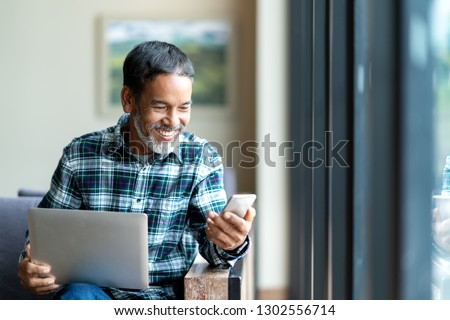 Candid of old asian retired man using mobile phone to transfer money online or financial payment and read text, smile or laugh with happy and positive. Senior asian with digital technology concept.