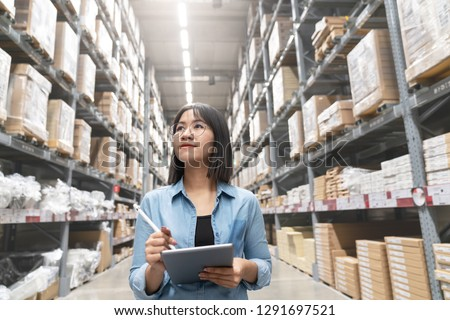 Candid of young attractive asian woman auditor or trainee staff work looking up stocktaking inventory in warehouse store by computer tablet with wide angle view. Asian owner or small business concept.