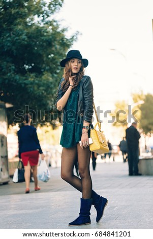Candid photo of stylish young tourist dressed in leather jacket, blue boots, black hat and yellow bag posing trendy with bent legs in public. Wearing analog watch with mobile phone on hand.
