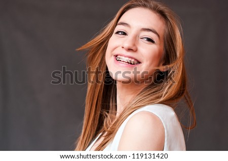 candid portrait of a girl wearing braces, with hair motion