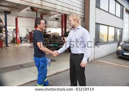 Candid portrait of a mechanic shaking hands with client
