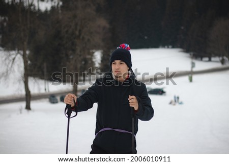 Candid portrait of a young ambitious man standing on top of mountain with trekking poles in Beskydy Mountains of the Czech Republic, Europe. A man aged 20-24 in a winter hat looking at top of mountain Foto stock ©