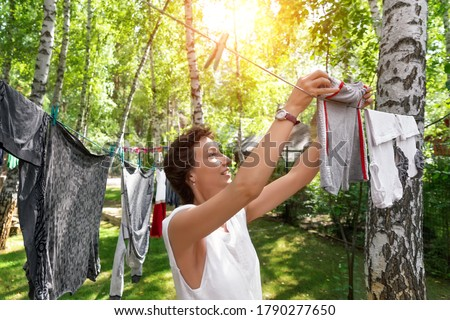 Candid real life portrait of young adult beautiful attractive caucasian woman hanging up fresh washed family clothes on birch tree clothesline with pins at home yard on bright sunny day outdoors Foto stock ©