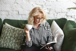 Candid shot of attractive senior female wearing stylish striped shirt and rectangular spectacles holding cup of tea and reading interesting book, sitting in modern living room interior alone