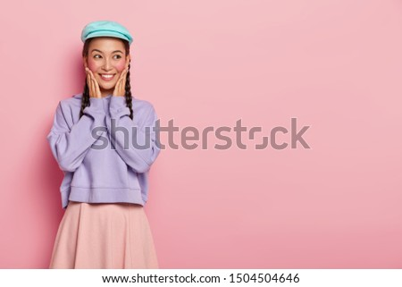 Candid shot of good looking young woman with appealing look, touches both cheeks, looks aside, wears blue cap, purple loose sweater and skirt, imagines something pleasant happened in future.