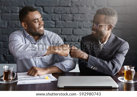 Candid shot of happy successful dark-skinned businessmen wearing formal clothing fist-bumping while cheering and congratulating each other after making profitable deal and signing good contract