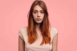 Candid shot of serious Caucasian female with freckled skin, dark eyes and long hair, wears casual clothing, poses against pink background. Adorable teenage girl poses in studio, being confident