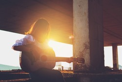 Candid silhouette woman chill play acoustic guitar musician Artists female sad mood activity music at balcony flare lighting sunset background