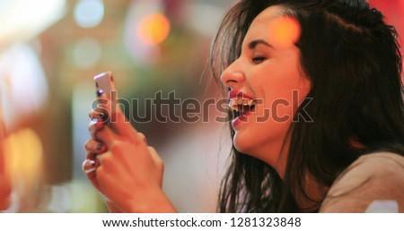 Candid surprise reaction of girl in front of cellphone reading text message smiling and laughing at night at coffee shop #1281323848
