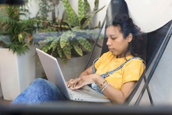 Candid view of young hispanic woman working with her laptop from home. Space for text.