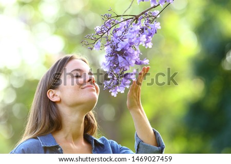 Candid woman smelling flowers standing in a park Foto d'archivio ©