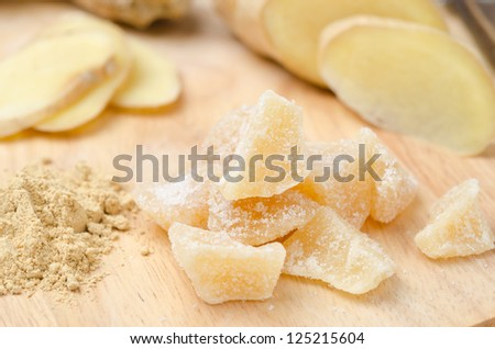 candied ginger on a wooden board closeup, ground and fresh ginger