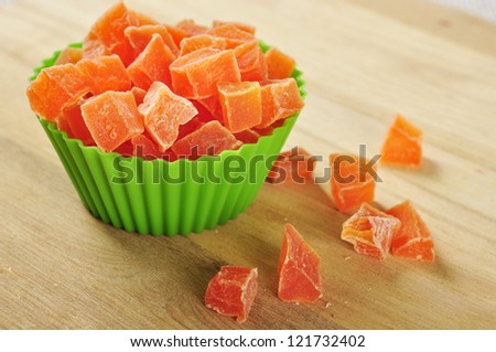 Candied papaya in green baking dish on wooden background.