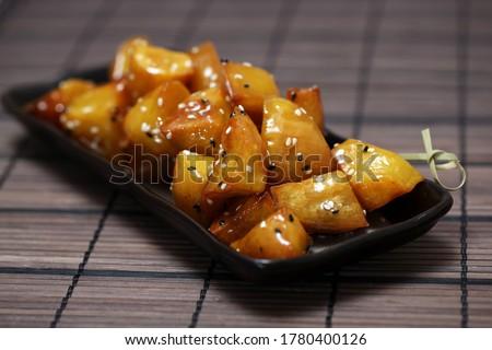 Candied Sweet Potato, Daigaku Imo, traditional Japanese food deep fried sweet potato coated with sweet syrup on the black plate. Fried sweet potato with honey