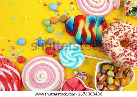 candies with jelly and sugar. colorful array of different childs sweets and treats on yellow Stock foto ©