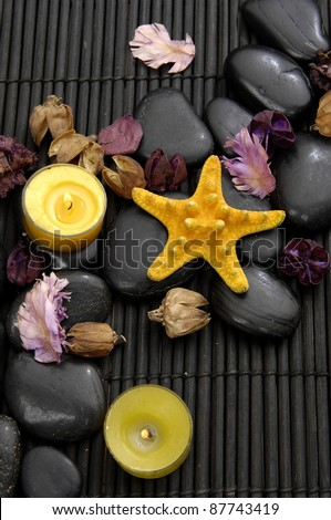 candle and massage stones and with petals with starfish on bamboo stick straw mat