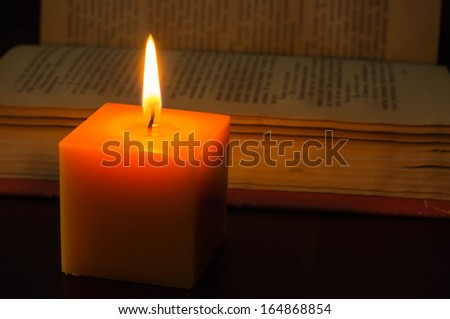 Candle and open book in the dark