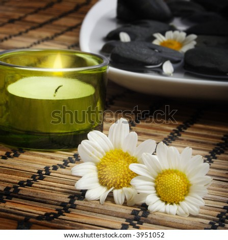 candle and two daisies before black pebbles. Black pebbles are in water in white plate.