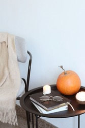 Candle, books and pumpkin on black table against a white wall. Concept of autumn home decor.