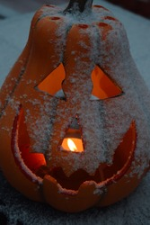 Candle burning in a snow covered jack o lantern