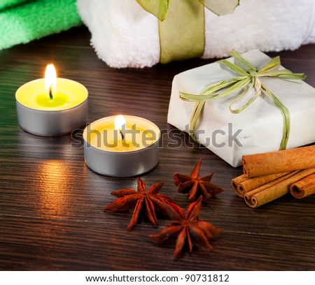 Candle, cinnamon sticks and anise stars with candle on table