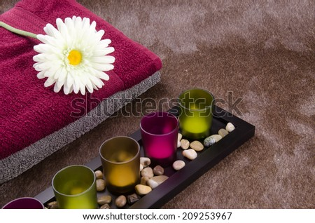 Candle container, towel, flower and aroma therapy flower on the sparkle brown Momento texture background: A concept and idea for interior design