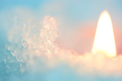 Candle flame in cold blue ice still life