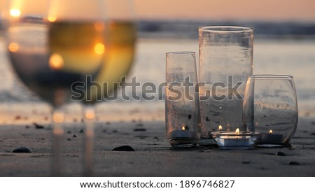 Photo of  Candle flame lights in glass, romantic beach date by California ocean waves, summer sea water. Candlelight seamless looped cinemagraph. Wineglass, glass with white wine on sand. Cozy lounge, sunset.