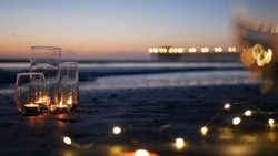 Candle flame lights in glass, romantic beach date, California ocean waves, sea water. Candlelight seamless looped cinemagraph. Wineglass on sand, garland in twilight dusk. Illuminated pier reflection.